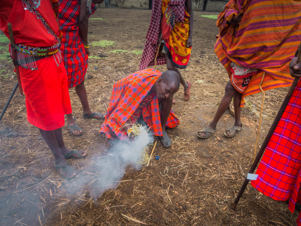 Travel - Visiting a Maasai Village - Kenyan Maasai Men demonstrate how to make a fire